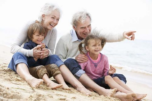 Older couple with their grandchildren at the beach
